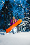 Young woman with her snowboard in the winter forest Royalty Free Stock Images