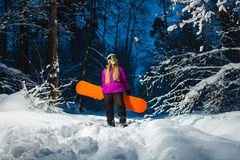 Young woman with her snowboard in the winter forest Stock Photos