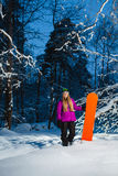 Young woman with her snowboard in the winter forest Stock Photography