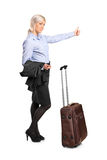 Young sexy woman hitchhiking. Isolated against white background Royalty Free Stock Photo