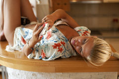 Young sexy woman laying on the bar typing on mobile phone Royalty Free Stock Image