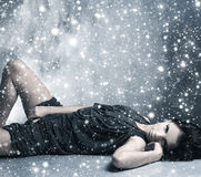 A young and sexy woman laying in a grey dress Royalty Free Stock Image