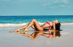 Young sexy woman lies on a beach in bikini Stock Image