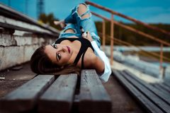 Young sexy woman lies on a wooden bench. She is taking break after workout in gym. Outdoor royalty free stock photo
