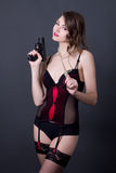 Young sexy woman in lingerie posing with gun over grey Royalty Free Stock Photo