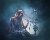 Young sexy woman in luxury underwear smoking a hookah Royalty Free Stock Image