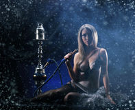 Young sexy woman in luxury underwear smoking the hookah Stock Image