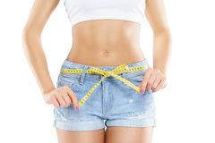 Young and sexy woman measuring her perfect body isolated on white. Nutrition, diet, concept. Stock Photos