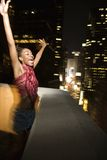 Young sexy woman in New York City, New York at night. Young sexy African-American woman jumping and screaming with excitement on patio in New York City, New Stock Photo