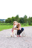 Young sexy woman playing  with puppy. Sexy woman playing in the park with golden retriever puppy Royalty Free Stock Image