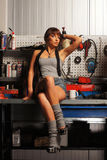 A young and sexy woman posing in a car garage Royalty Free Stock Image