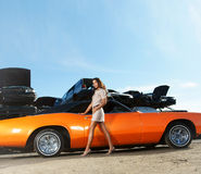 Young and sexy woman posing near a muscle car Royalty Free Stock Image