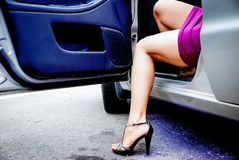 Young sexy woman get out of the car. Young sexy woman in purple dress get out of the car Stock Photos