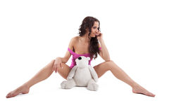 Young sexy woman in purple shirt with white bear. Young sexy woman in purple shirt doing split on white with bear Royalty Free Stock Image