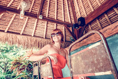 Young woman in red dress in a tropical cafe on the background of a palm trees and tropical plants. Bali, Indonesia. Royalty Free Stock Images