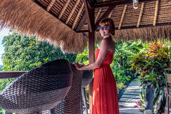 Young sexy woman in red dress in a tropical cafe on the background of a palm trees and tropical plants. Bali, Indonesia. Royalty Free Stock Image