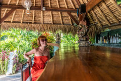 Young woman in red dress in a tropical cafe on the background of a palm trees and tropical plants. Bali, Indonesia. Royalty Free Stock Image