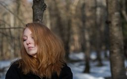 Young sexy woman with red hair and head down, with black clothes, is standing sad, depressed, desperate in winter stock images