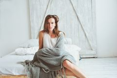 Young sexy woman relaxing at home in bed in cozy winter weekend morning. Wrapped in warm knitted blanket Royalty Free Stock Image