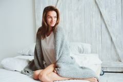 Young woman relaxing at home in bed in cozy winter weekend morning stock photography