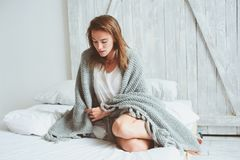 Young sexy woman relaxing at home in bed in cozy winter weekend morning. Wrapped in warm knitted blanket Stock Photography