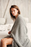 Young sexy woman relaxing at home in bed in weekend morning, wrapped in knitted blanket Stock Photo