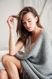 Young sexy woman relaxing at home in bed in weekend morning, wrapped in knitted blanket Stock Images