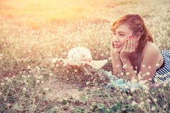 Young woman resting on the flower field and smile stock photo