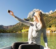 Woman is rowing with a rowing boat with a lake in the mountains. Young sexy woman is rowing with a rowing boat on a lake in the beautiful mountains. a wonderful Stock Photography
