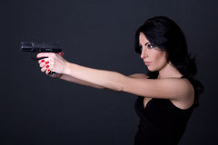 Young sexy woman shooting with gun over grey Royalty Free Stock Images