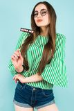 Young sexy woman with sign kiss me on stick. Portrait of attractive brunette young woman with in green striped shirt, glasses and jeans shorts on blue background Royalty Free Stock Image