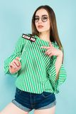 Young sexy woman with sign kiss me on stick. Portrait of attractive brunette young woman with in green striped shirt, glasses and jeans shorts on blue background Stock Photo