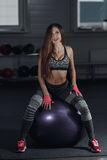 Young sexy woman sit on fitness ball in gym and looking at camera. Stock Photo