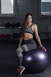 Young sexy woman sit on fitness ball in gym and looking at camera. Royalty Free Stock Images
