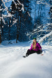 Young woman sitting on her snowboard in the winter forest Stock Photo