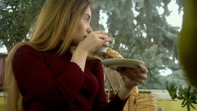 Young sexy woman sitting at home in a wicker chair looking out the window with snowfall behind it and enjoying a cup of stock footage