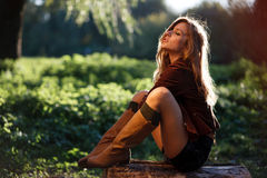 Young woman sitting on log Stock Photo