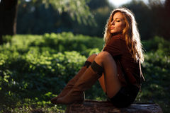 Young sexy woman sitting on log posing Royalty Free Stock Photography