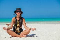 Young sexy woman sitting in the lotus position on Royalty Free Stock Photography