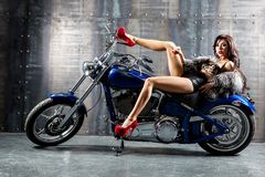Young sexy woman sitting on motorcycle. Stock Photo
