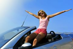 Young woman sitting on top of cabrio sport car in summer vacation with arms open to the air Stock Image