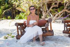 Young sexy woman sitting on wooden chair in exotic Royalty Free Stock Photos
