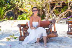 Young sexy woman sitting on wooden chair in exotic Stock Photography