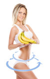 Young sexy woman in sporty clothes with an exotic fruit. Female body with the drawing arrows on it isolated on white. Healthy eating concept Stock Photos