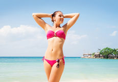 Young and sexy woman standin in the sea on the beach Royalty Free Stock Images