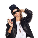 Young sexy woman in sunglasses and black leather jacket smoking cigar Royalty Free Stock Photos