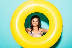 Young woman in swimsuit inside inflatable ring a isolated over green background royalty free stock image