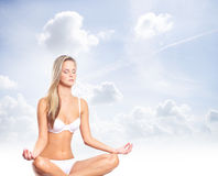 Young sexy woman in swimsuit meditating Stock Image