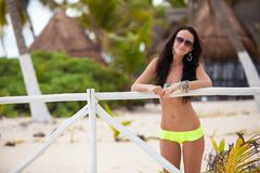 Young sexy woman in swimsuit near white fence at Royalty Free Stock Photo