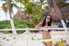 Young sexy woman in swimsuit near white fence in Stock Photos